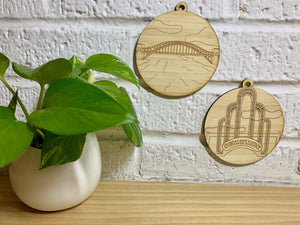 Shown on a white brick wall and next to a houseplant are two laser cut wall hangings. It is cut from bamboo, a fast growing and sustainable grass. Etched in one is a picture of the iconic Sunnyside Arch in the center of the Queens neighborhood. The other shows the Hell Gate Bridge in Astoria. Each piece can be painted like a paint by number or left plain. It can hang from your Christmas Tree or on you wall all year round.