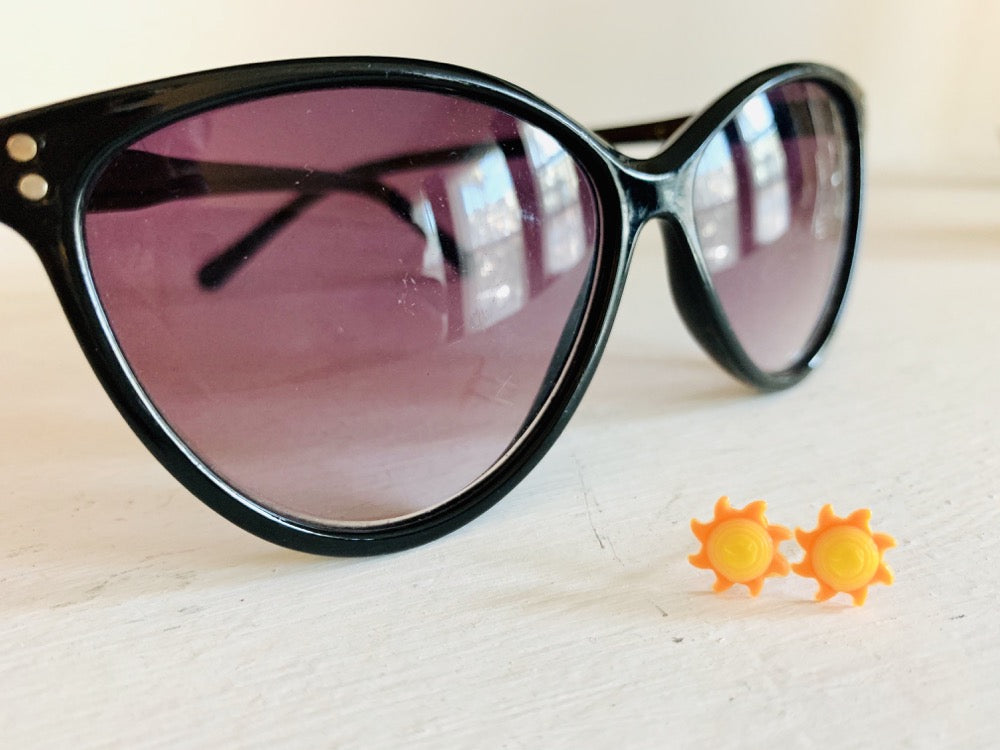 In the foreground are two small stud earrings. They are shaped as suns with bright yellow centers that are rounded and eight sun rays that curl around the sun in orange. In the background are a pair of black sunglasses.