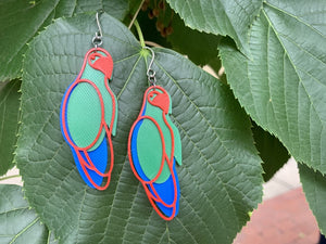 Hanging off of a large lush green leaf are two R+D earrings. The earrings are made from three pieces , one cobalt blue, one kelly green, and the final, which rests on top of the other is bright red and creates the outline of a parrot.