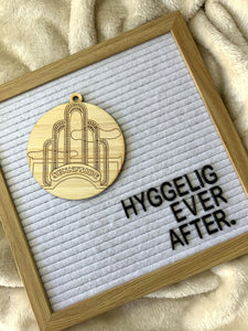 "Shown on a cozy blanket is a letter board that reads ""Hyggelig Ever After."" There is also a laser cut wall hanging. It is cut from bamboo, a fast growing and sustainable grass. Etched in it a picture of the iconic Sunnyside Arch in the center of the Queens neighborhood. Each piece can be painted like a paint by number or left plain. It can hang from your Christmas Tree or on you wall all year round."