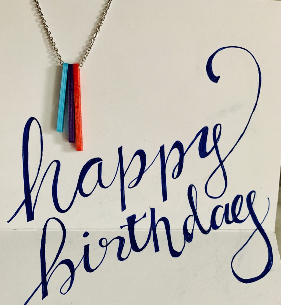 Hanging in a card with the words, happy birthday scrawled, is a necklace with three pendants. They are long rectangles in teal, purple, and red. When turned to the side, each pendant reveals a name.