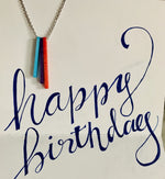 Load image into Gallery viewer, Hanging in a card with the words, happy birthday scrawled, is a necklace with three pendants. They are long rectangles in teal, purple, and red. When turned to the side, each pendant reveals a name.