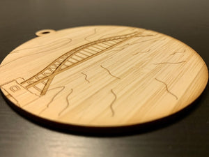 Shown from the side so you can see the detail is a laser cut wall hanging. It is cut from bamboo, a fast growing and sustainable grass. Etched in it a picture of the Hell Gate bridge in Astoria. This bridge is an icon of the area and looked on from Asttoria Park. This can be used as a ornament in the holidays or a wall hanging all year round. It can be painted like a paint by number or left plain.