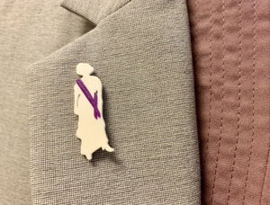 On the lapel of a grey suit is a 3D printed R+D pin. It is the silhouette of a woman from the 1910s wearing a long dress, hat, and heels. Her silhouette is in white, but there is a bright purple sash across her body to show she is a suffragette.