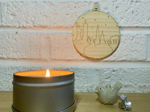 Shown on a white brick wall next to a candle and the knick knacks, is a laser cut wall hanging. It is cut from bamboo, a fast growing and sustainable grass. Etched in it a picture of the New York City Skyline with the Statue of Liberty, Empire State Building, Chrysler Building and Brooklyn Bridge all visible. Each piece can be painted like a paint by number or left plain. It can hang from your Christmas Tree or on you wall all year round.