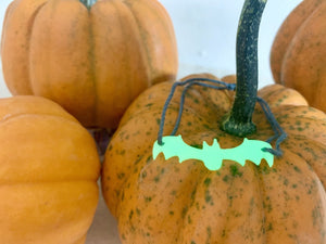 In this picture there are multiple pumpkins all around. On top of one is a bracelet. It has a dark grey adjustable cord that is holding on to a 3D printed bat that glows in the dark.