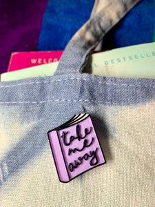 There is a close up of a cotton tote bag with a blue and white shibori pattern. Spilling out of the bag are a couple of paperback books suitable for reading on the beach. Attached to the tote bag is a 3D printed pin shaped like a floppy well read book. The pin is light purple with white pages and black details. On the cover ar scripted cursive words that say take me away.