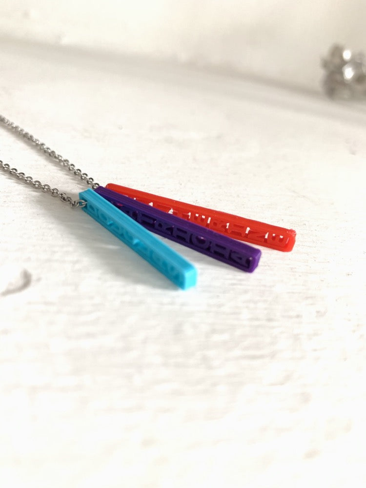 On a white background are three 3D printed pendants. They are each different colors and shaped as long rectangles with names in the center. When worn, they simply look like long hanging rectangles, but from the side, all the names are visible. This one has a teal pendant, a purple pendant, and a red pendant.