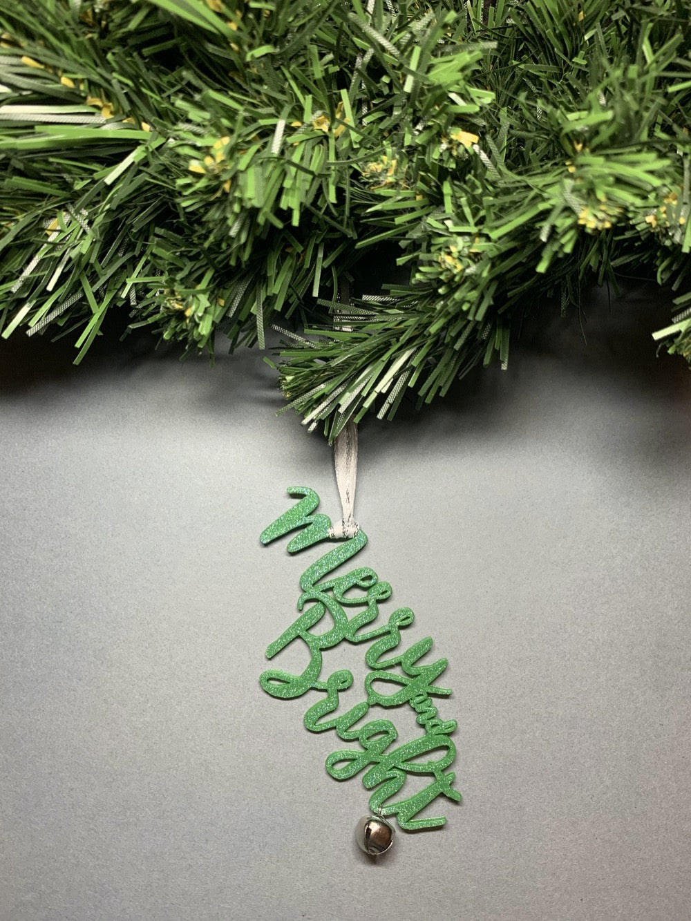 On a grey background and hanging from a green wreath is a 3D printed R+D ornament. It is a cursive text with a jingle bell and covered in glitter to make it shimmer and shine in the light. This ornament reads, Merry and Bright.