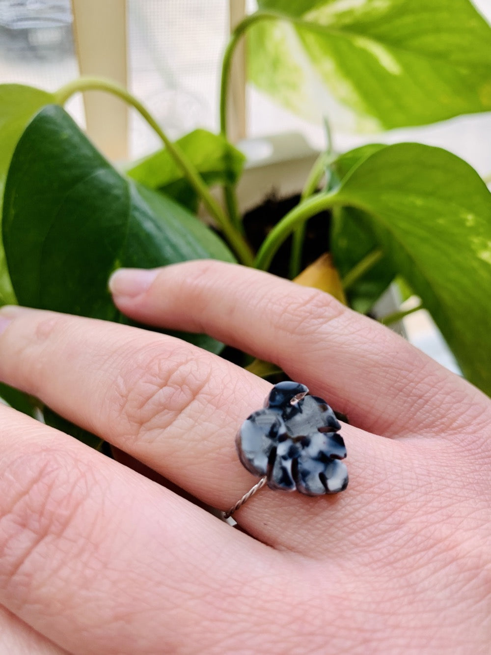 In the foreground is a hand with a ring cast from recycled plant based 3D prints. It is a ring in the shape of a monstera leaf with black, white, and silver filaments being used to create a speckled look like granite. In the background are bright green leaves.