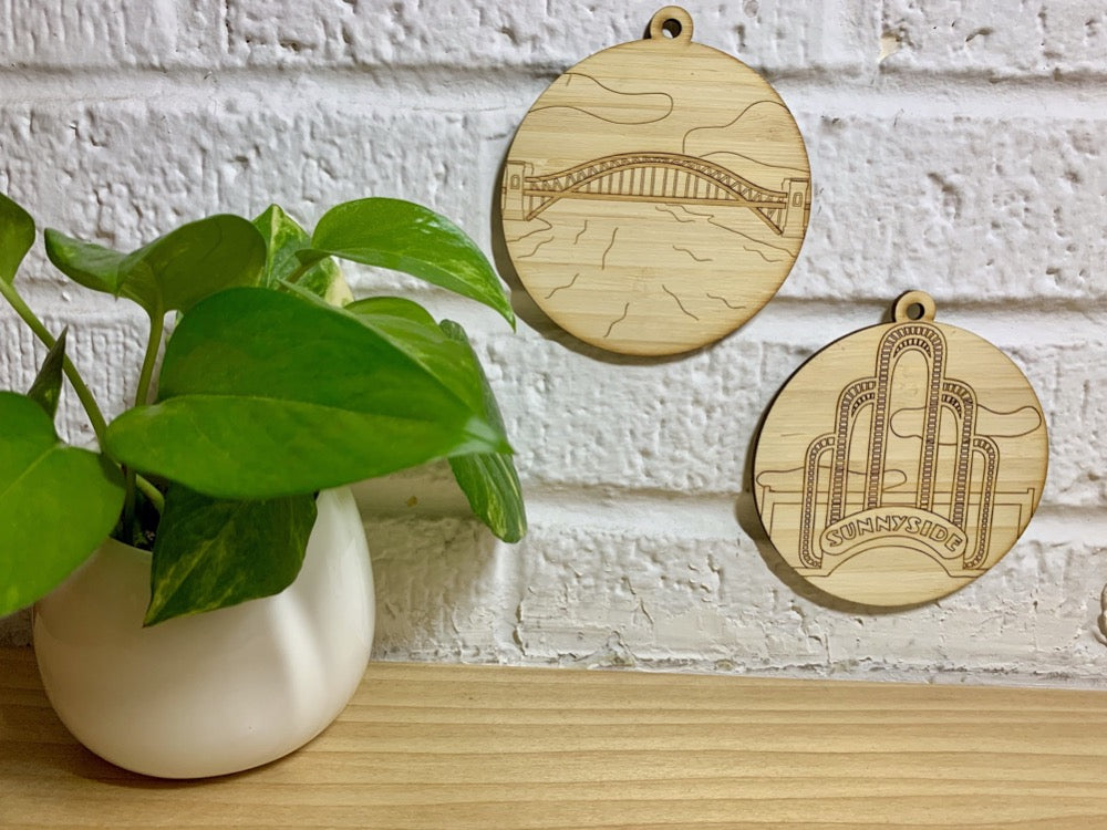 Hanging on a white brick wall and next to a houseplant are two laser cut wall hangings. They are each cut from bamboo, a fast growing and sustainable grass. Etched in one is a picture of the Hell Gate bridge in Astoria. This bridge is an icon of the area and looked on from Asttoria Park. The other features the sunnyside arch on Queens Blvd. These can be used as a ornament in the holidays or a wall hanging all year round. It can be painted like a paint by number or left plain.
