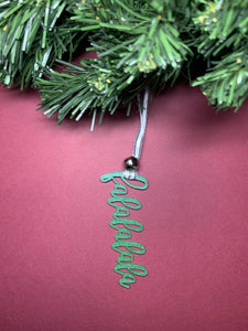 On a bright red background and hanging from a green wreath is a 3D printed R+D ornament. It is a cursive text with a jingle bell and covered in glitter to make it shimmer and shine in the light. This ornament reads, falalalala.