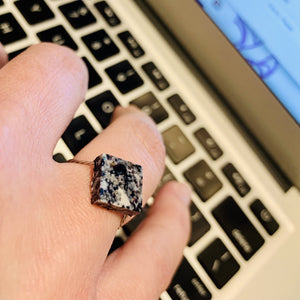 Shown on someone's finger as they type on a computer keyboard is a cast ring. The ring is a square shape with a smooth surface. It is made from recycled 3D prints that were black, white, and silver. It has a speckled look like granite.