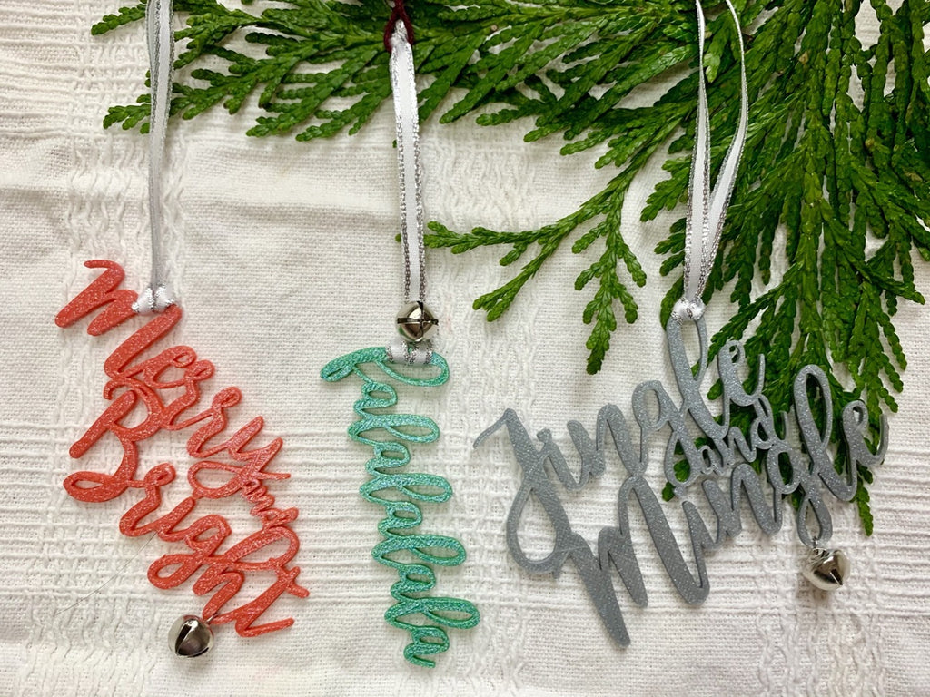 "On a white fabric background there are three R+D 3D printed ornaments hanging from an evergreen branch. Each is in a cursive font and have a jingle bell attached. There are in red, green or silver colors and read ""Merry and Bright"", ""falalalala"", and ""Jingle and Mingle"""