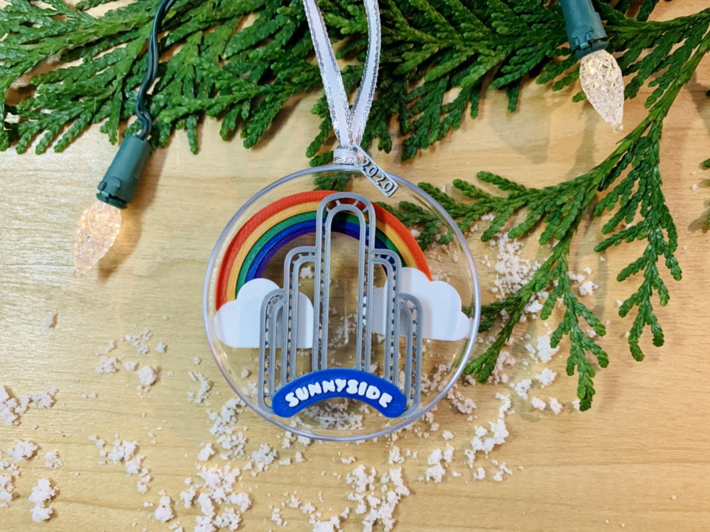 On a wooden shelf, there is a sprig of greenery, Christmas tree lights, and some scattered snow.Laying on top is a ornament with a small tag that has been 3D printed to read 2020. Inside the half circle ornament is a rainbow spanning between two clouds and the iconic Sunnyside Arch in front of it.