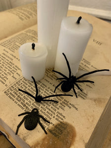 Shown are two black spider earrings that are realistic in their shape. They are worn as front and back earrings. One of the earrings has the two pieces separated to show how they would be then worn on each side of your earlobe. They are pictured crawling up an old book with candles on top to create a spooky Halloween scene.
