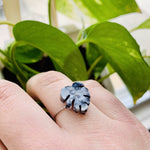 Load image into Gallery viewer, In the foreground is a hand with a ring cast from recycled plant based 3D prints.  It is a  ring in the shape of a monstera leaf with black, white, and silver filaments being used to create a speckled look like granite. In the background are bright green leaves.