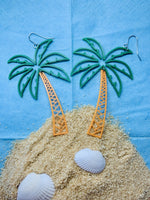 Load image into Gallery viewer, In front of a bright sky blue background is a mound of sand like an island. There are white shells in the sand. At the top of the mound are two 3D printed R+D earrings that are shaped like palm trees. The fronds are kelly green and burst out in a lively way. The trunks are orange and curve to the swaying top.