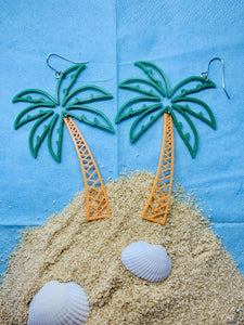 In front of a bright sky blue background is a mound of sand like an island. There are white shells in the sand. At the top of the mound are two 3D printed R+D earrings that are shaped like palm trees. The fronds are kelly green and burst out in a lively way. The trunks are orange and curve to the swaying top.