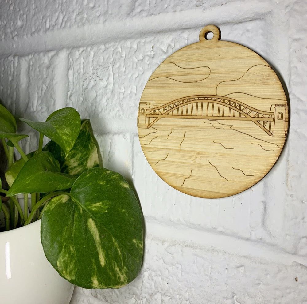 Hanging on a white brick wall and next to a houseplant is a laser cut wall hanging. It is cut from bamboo, a fast growing and sustainable grass. Etched in it a picture of the Hell Gate bridge in Astoria. This bridge is an icon of the area and looked on from Asttoria Park. This can be used as a ornament in the holidays or a wall hanging all year round. It can be painted like a paint by number or left plain.