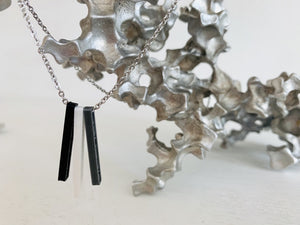 Shown on a white background with an aluminum sculpture, there is a necklace with 3 3D printed pendants. The pendants are long and thin, in silver, white, and black. When turned to the side, names are visible on the pendants.
