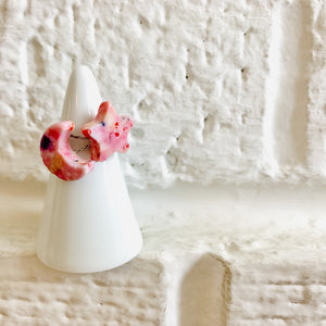 On painted white bricks is a white ring holder with two cast rings on it. One ring is shaped like a moon, the other a star. They are cast from recycled 3D printed pieces in various warm and pink hues.