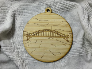 Shown on a white fabric background is a laser cut wall hanging. It is cut from bamboo, a fast growing and sustainable grass. Etched in it a picture of the Hell Gate bridge in Astoria. This bridge is an icon of the area and looked on from Asttoria Park. This can be used as a ornament in the holidays or a wall hanging all year round. It can be painted like a paint by number or left plain.