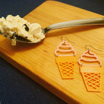 Load image into Gallery viewer, Two ice cream cone earrings are laying on a wooden cutting board next to a spoon piled with ice cream. The earrings have pink tops swirled like soft serve and orange bottoms that look like a sugar cone.