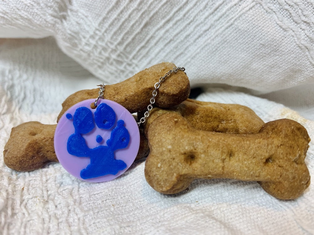 Shown on white fabric is a pile of dog bone treats. In front of that is a 3D printed pendant. The pendant is a 1 inch circle that is light purple. Printed on the pendant is a blue paw print that is customized.