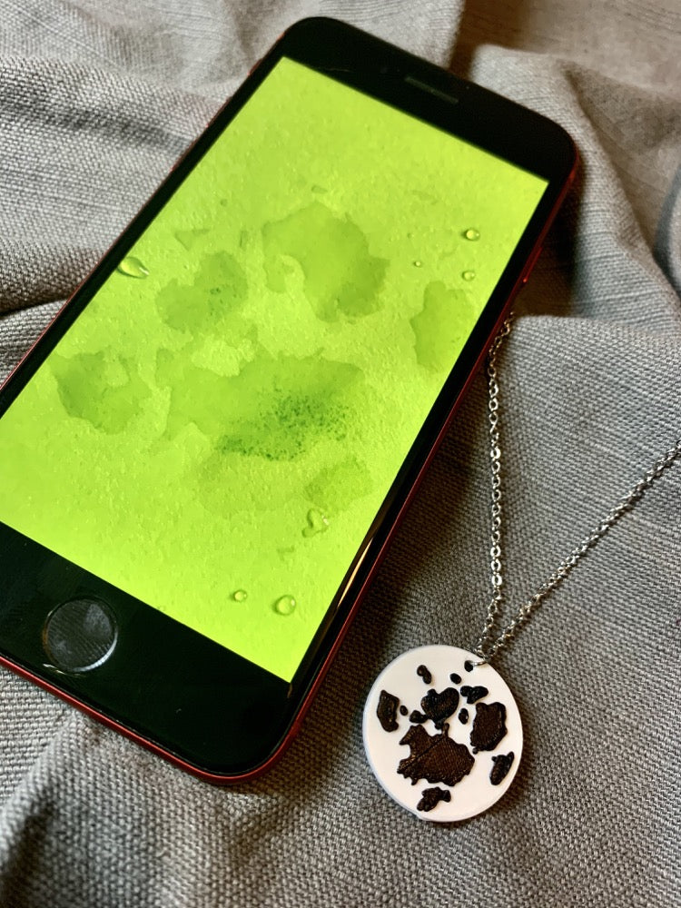 On a grey fabric background is a phone and a necklace with a 3D printed pendant. The pendant is white and has a black paw print printed on it. The phone has an image showing on the phone -- it is the same paw print that is used to make the design on the pendant.