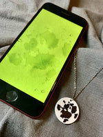 Load image into Gallery viewer, On a grey fabric background is a phone and a necklace with a 3D printed pendant. The pendant is white and has a black paw print printed on it. The phone has an image showing on the phone -- it is the same paw print that is used to make the design on the pendant.
