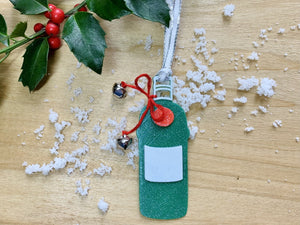 Shown on a wood background with a sprig of holly and white snow is a 3D printed R+D ornament. It is in the shape of a gin bottle: green with a white label and a red emblem. Tied around the neck is a red bow that has two jingle bells attached. The entire ornament is covered in glitter to give it a shimmer and shine.