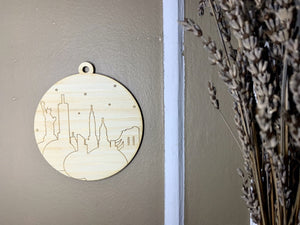 Shown on a brown wall with drip lavender to the side is a laser cut wall hanging. It is cut from bamboo, a fast growing and sustainable grass. Etched in it a picture of the New York City Skyline with the Statue of Liberty, Empire State Building, Chrysler Building and Brooklyn Bridge all visible. Each piece can be painted like a paint by number or left plain. It can hang from your Christmas Tree or on you wall all year round.