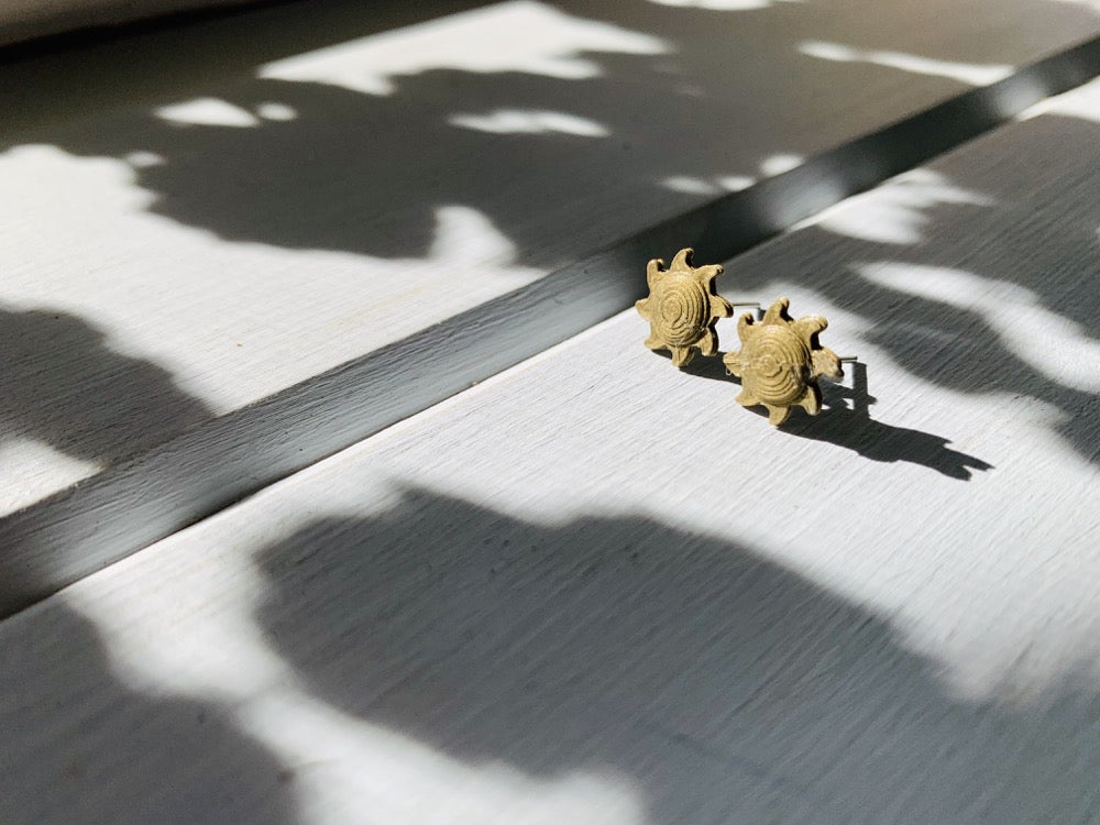 Shown in the bright afternoon sun are two gold 3D printed earrings shaped like suns. They are in a sun beam, but surrounded by shadows casting from plants.