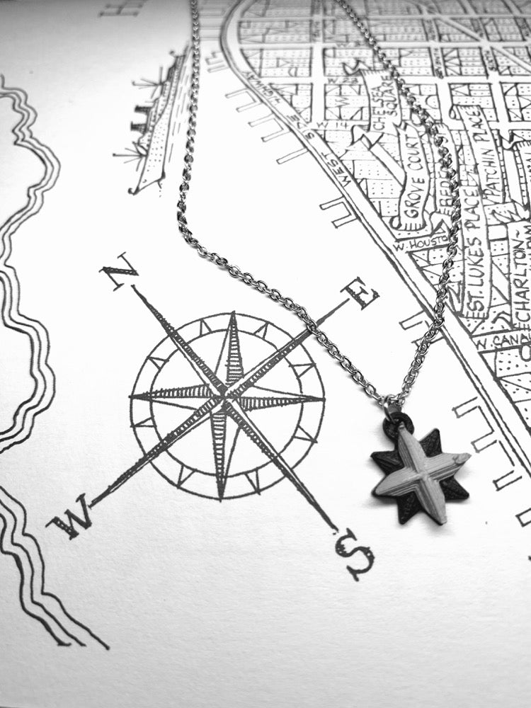 Laying across a drawn map and compass is an R+D necklace. The necklace is black and silver and shaped like a compass with 8 points.