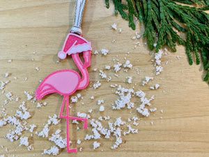 On a wooden shelf with sprigs of evergreen and white snow is a R+D 3D printed ornament. It is a bright pink flamingo that has one leg up and is wearing a hot pink santa hat.