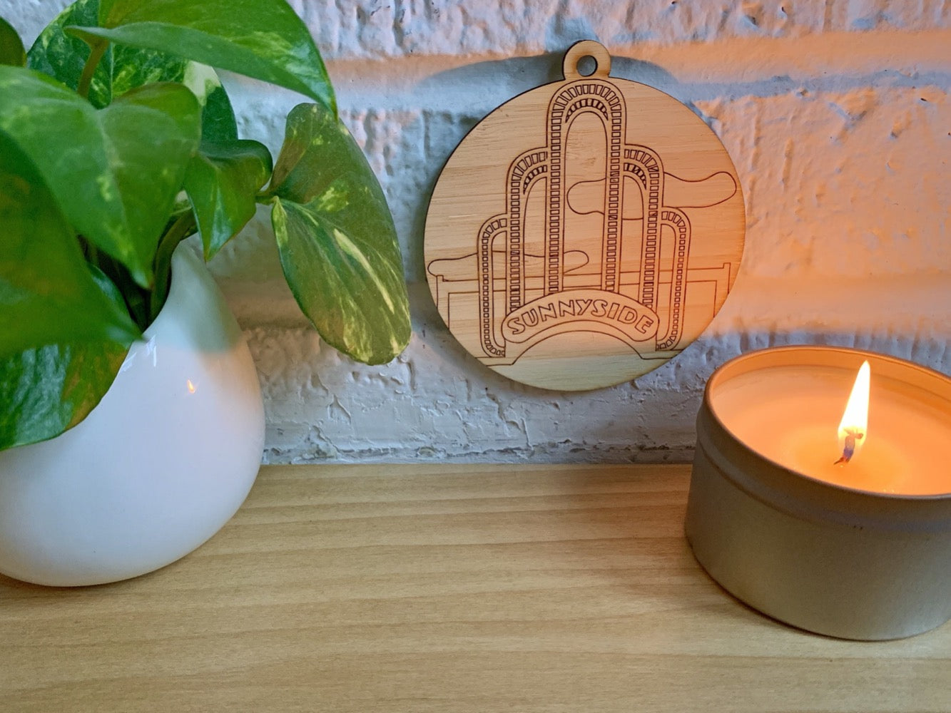 Shown on a white brick wall and above a wood shelf with a house plant and a candle is a laser cut wall hanging. It is cut from bamboo, a fast growing and sustainable grass. Etched in it a picture of the iconic Sunnyside Arch in the center of the Queens neighborhood. Each piece can be painted like a paint by number or left plain. It can hang from your Christmas Tree or on you wall all year round.