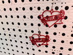 Load image into Gallery viewer, Two earrings are hanging off of a background with white paint and holes across it. The earrings are a dark merlot red and shaped like heart tattoos--they are hearts with a banner twisting around it and two roses. The banner reads outlaw, but can be personalized to any word. They are 3D printed in an eco friendly filament.