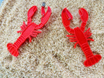 Load image into Gallery viewer, Shown on a bed of sand are two 3D printed R+D earrings. The earrings are bright red and shaped like lobsters. The larger crusher claw on the lobster wraps around the earlobe when being worn.