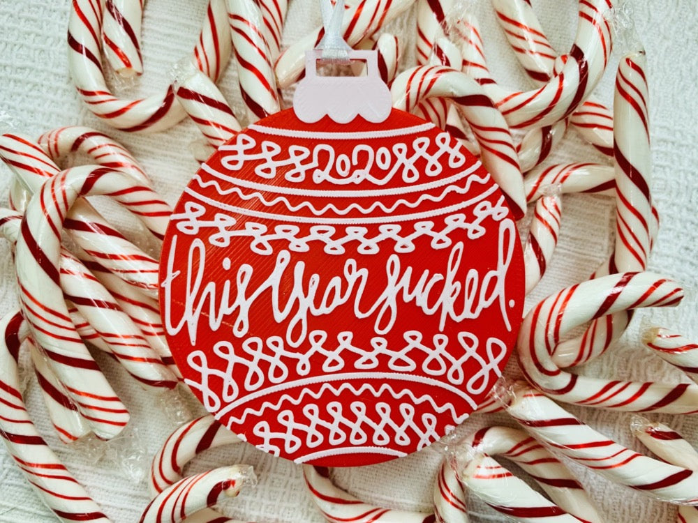 "On a white fabric background there are lots of red and white peppermint candy canes and a R+D 3D printed ornament. The ornament is shaped like a traditional bulb. It is bright red with white drawings and script on it. Worked into the doodles are the year 2020 and then the words, ""this year sucked""."