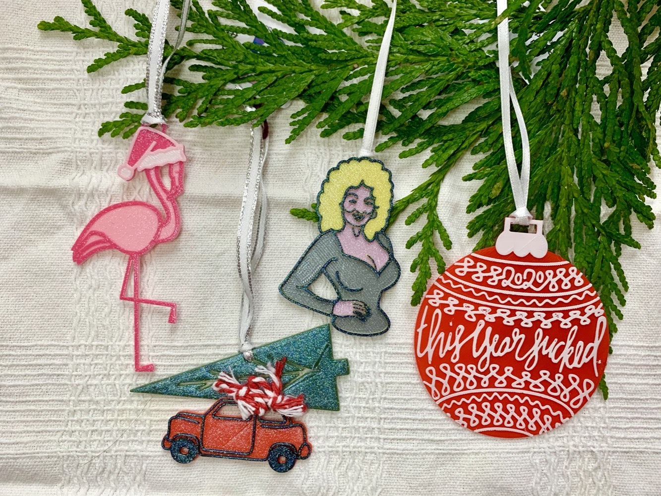 "On a white fabric background is a evergreen branch. There are four ornaments hanging from it. Each of the ornaments are 3D printed R+D ornaments and made with plant based filament. The first is a bright pink flamingo wearing a santa hat. The second is a vintage style red car with a christmas tree on the roof. The third is Dolly Parton. The final is a red bulb that has lines and drawings all over it. It is includes ""2020"" and ""This year sucked"""