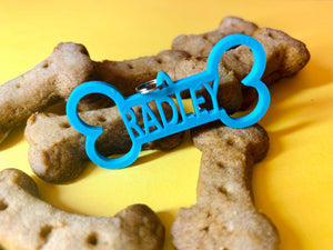 Pictured on a yellow background with dog treats shaped like bones is a 3D printed dog tag. The tag is bright teal and also shaped like a dog bone and have the name RADLEY in the middle. It can be customized to any pets name.