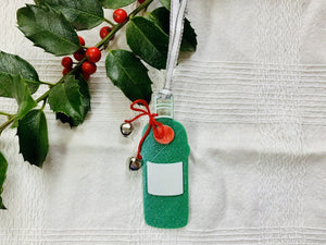 Shown on a white fabric background with a sprig of holly is a 3D printed R+D ornament.  It is in the shape of a gin bottle: green with a white label and a red emblem. Tied around the neck is a red bow that has two jingle bells attached. The entire ornament is covered in glitter to give it a shimmer and shine.