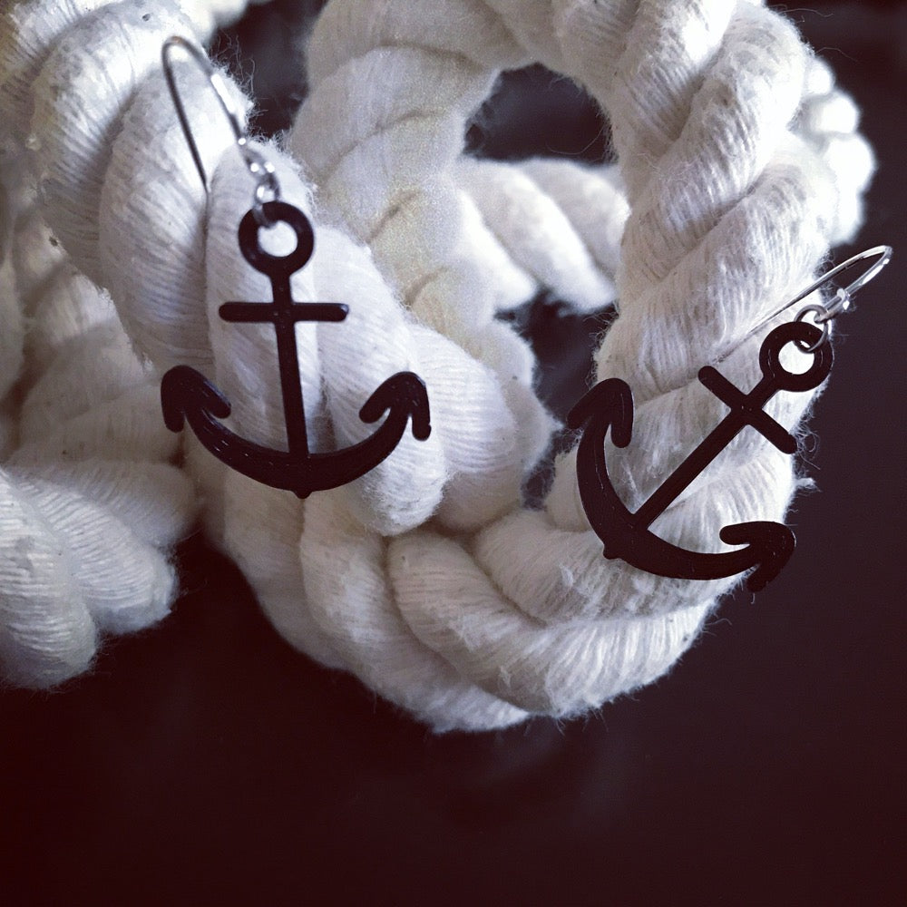 Two black earrings are shown on a thick cotton rope. The earrings are shaped like anchors and 3D printed using a environmentally friendly material made from corn.
