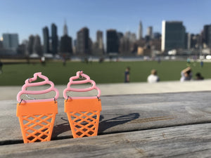 Two ice cream cone shaped earrings are perched between slats of a wooden bench. The top is pink and looks like soft serve swirled into a orange sugar cone. In the background, you can see a park with people enjoying the sun and the Manhattan skyline.