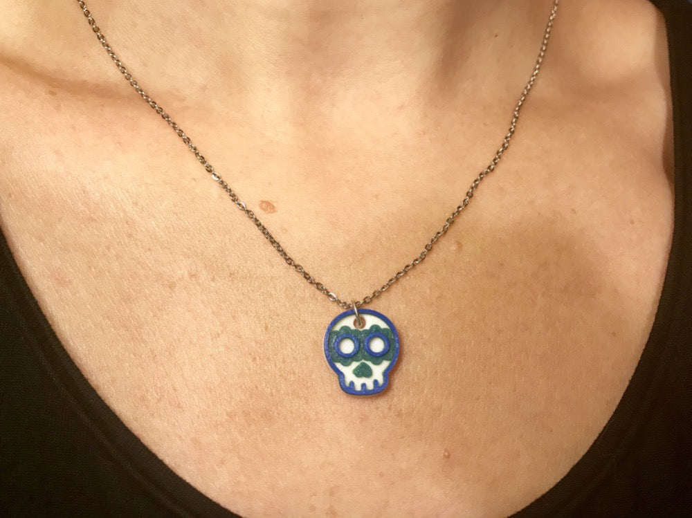 A necklace is being shown worn around someone's neck. There is a thin chain and a 3D printed pendant. The pendant is a small sugar skull that is white, green, and blue.
