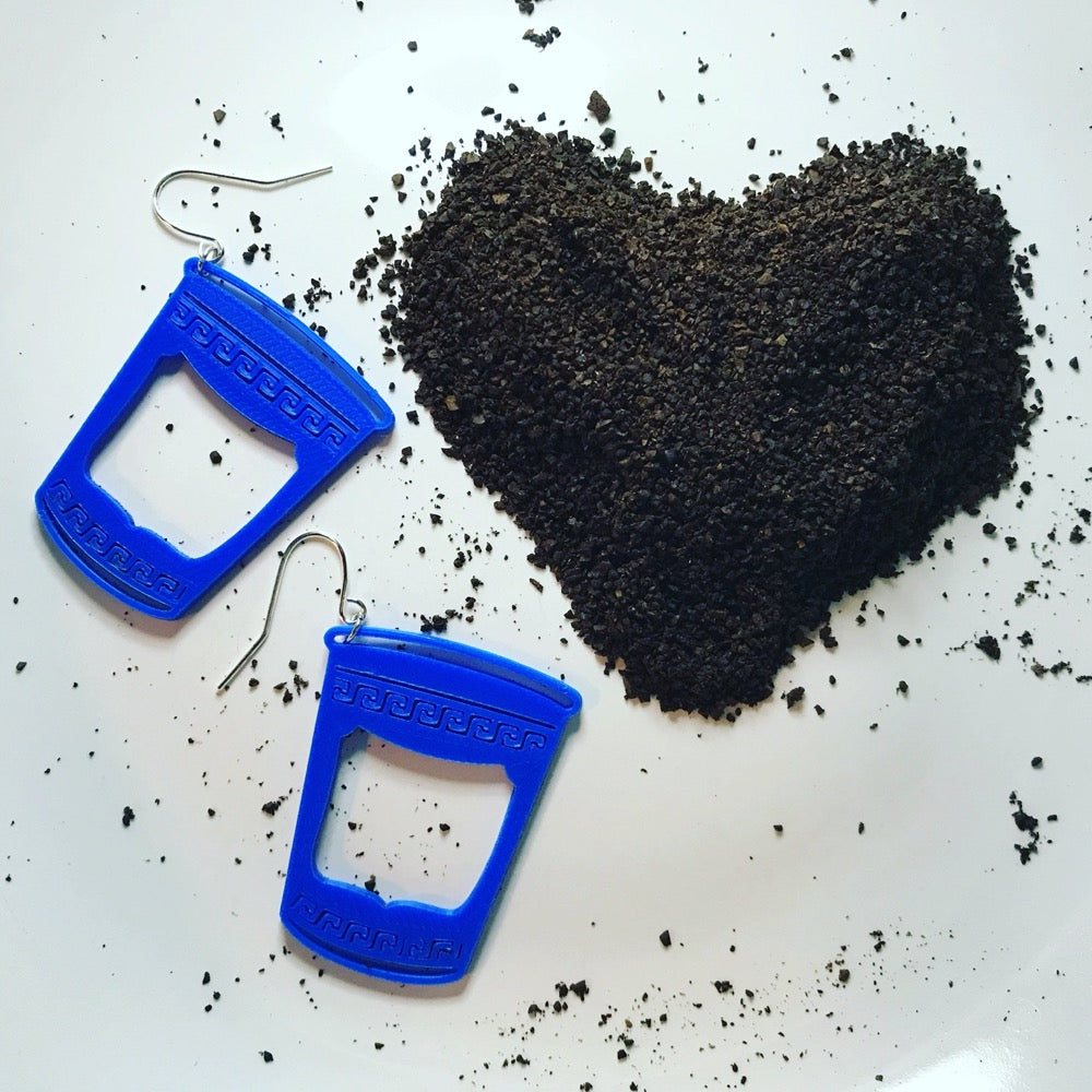 Two bright blue earrings that are shaped like iconic Greek to-go coffee cups in New York City. The NYC bodega cups are next to a heart formed from coffee grounds.