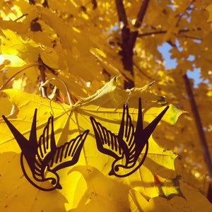 Hanging off of a bright yellow fall tree are two black R+D swallow earrings. These birds look like classic sailor tattoos, swooping down like they are flying.