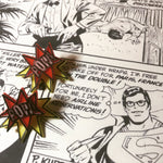 Load image into Gallery viewer, On a black and white comic book page with Superman/Clark Kent are two R+D earrings. They are front back earrings or ear jackets where there is a piece that hugs each side of the earlobe. The front shows a ref star burst that reads POW! in white. It is all outlined in black. The piece that fits behind the ear is a yellow starburst with a black outline. They are meant to look like a classic comic book illustration of a sound.