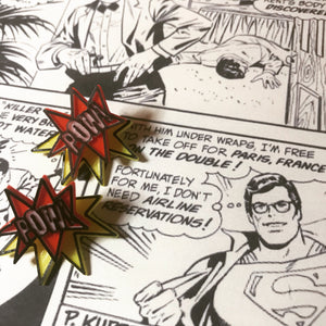 On a black and white comic book page with Superman/Clark Kent are two R+D earrings. They are front back earrings or ear jackets where there is a piece that hugs each side of the earlobe. The front shows a ref star burst that reads POW! in white. It is all outlined in black. The piece that fits behind the ear is a yellow starburst with a black outline. They are meant to look like a classic comic book illustration of a sound.